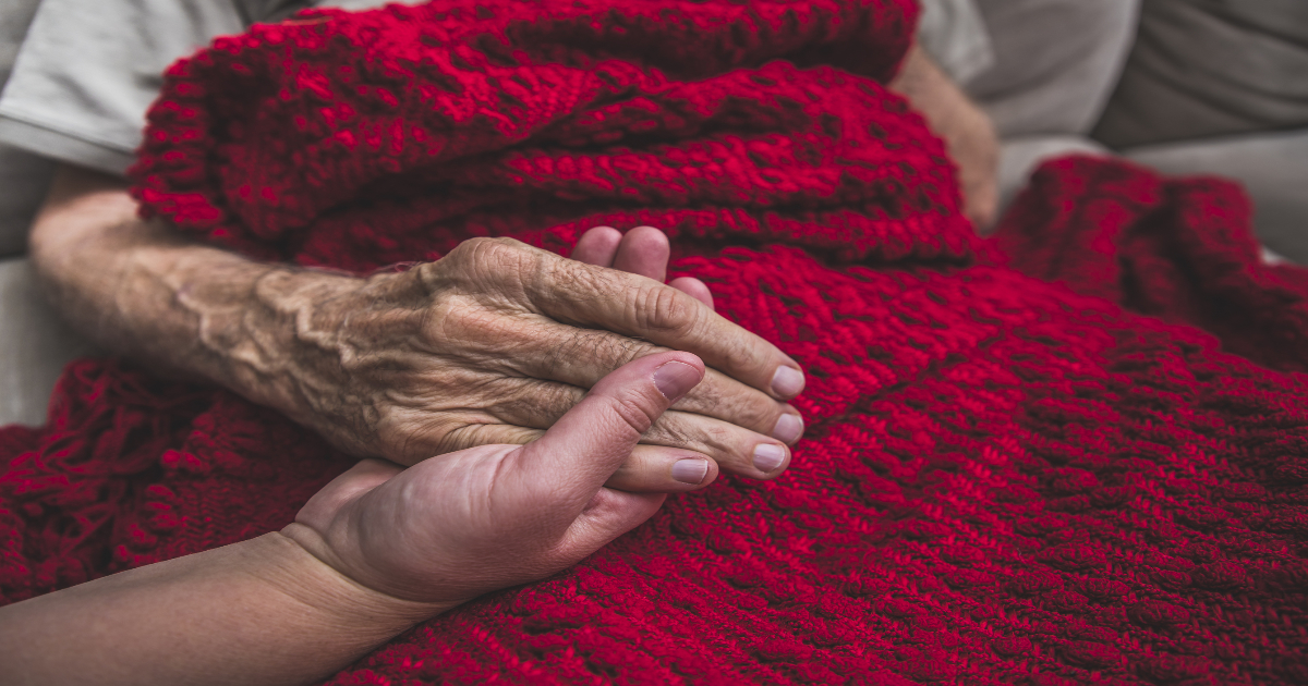 An elderly individual rests their hand on a loved ones hand on a red blanket